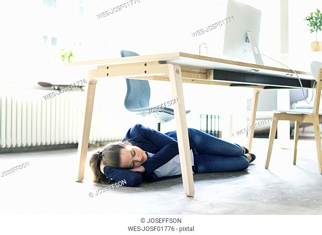 Businesswoman lying under the table in office sleeping
