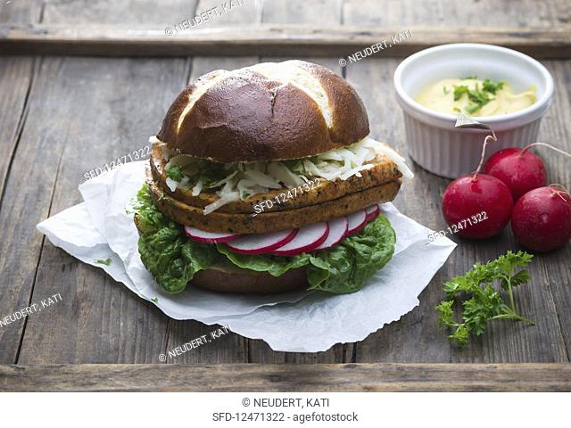 A lye bread roll with vegan meatloaf, coleslaw, radishes, lettuce and mustard