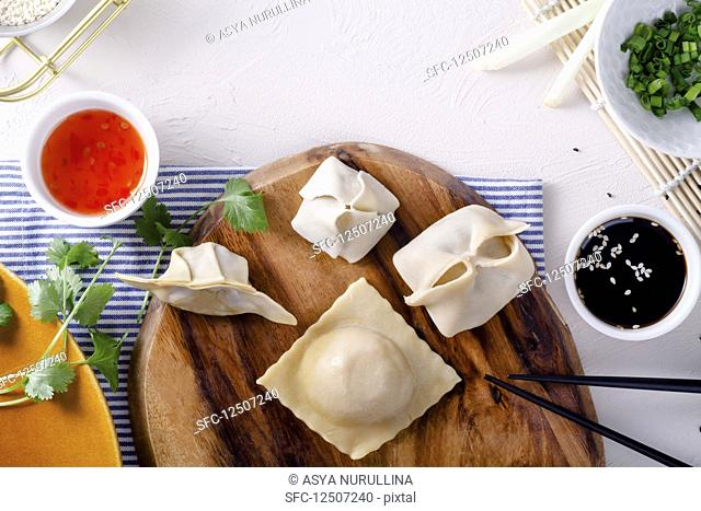 Various raw dumplings on a wooden board next to two sauces (seen from above)