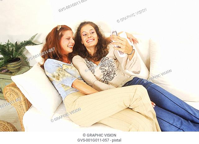 Two young women playing with a mobile phone