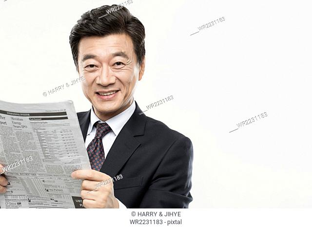 Senior man in black suit holding newspaper and smiling
