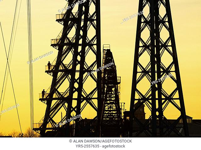 Workmen on Tees Transporter bridge silhouetted against setting sun. Middlesbrough, north east England, United Kingdom. The Tees Transporter Bridge is one of...