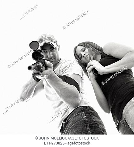 Man and women with guns; aiming at lens