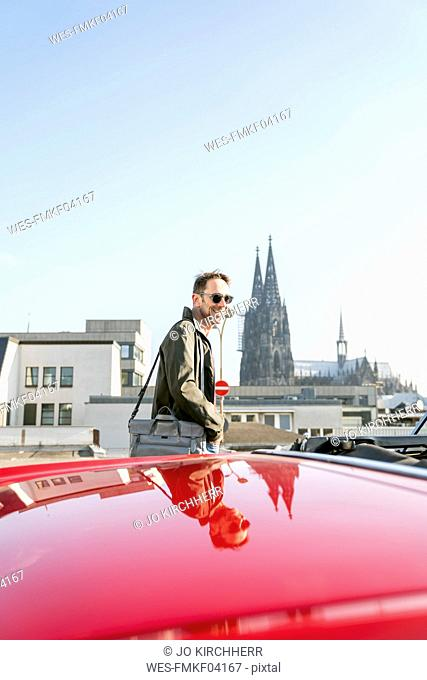 Germany, Cologne, portrait of smiling mature man with his parked sports car