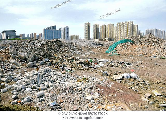 Inner city redevelopment Taiyuan city, Shanxi Province, China. Demolition debris from old hutong ghetto clearance. New high rise accommodation behind