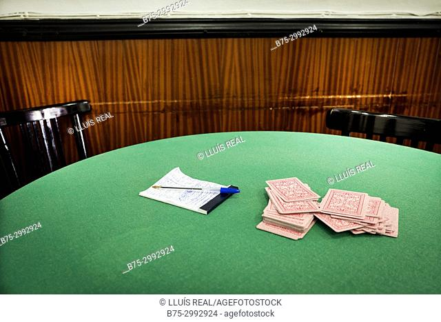 Green poker table with playing cards, notepad and ballpoint pen on it