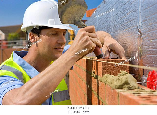 Bricklayer setting brick wall with trowel