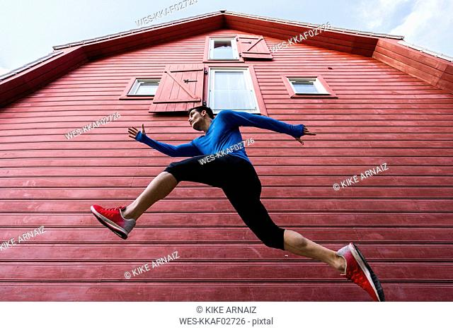 Low angle view of sportive man exercising in front of red house