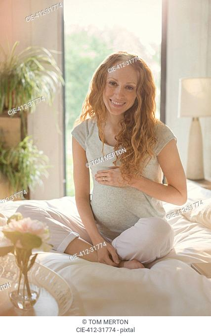 Portrait smiling pregnant woman sitting on bed