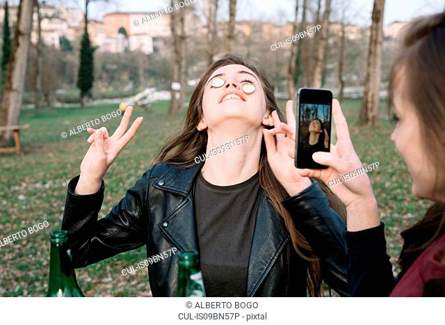 Woman taking photograph of friend balancing bottle caps on cheeks