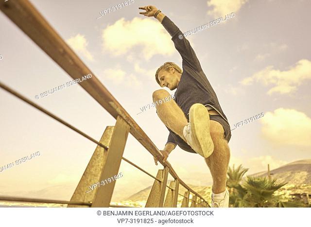 Man jumping over handrail, Stalida, Crete, Greece
