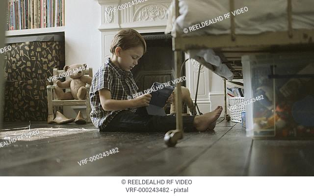 Boy sitting and playing with digital tablet in room