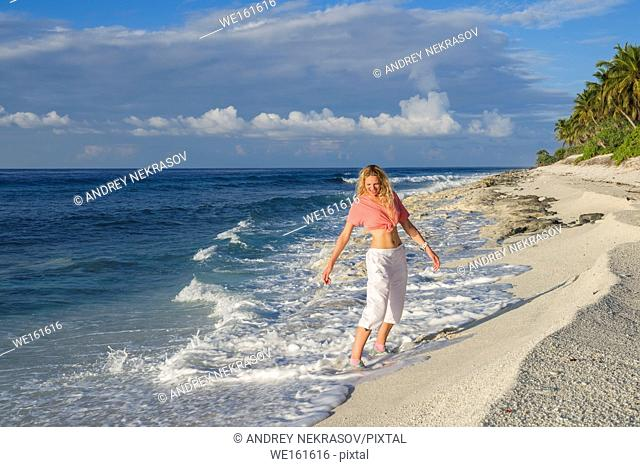 Young beautiful woman on a coral beach. Fuvahmulah island, Indian Ocean, Maldives, Asia