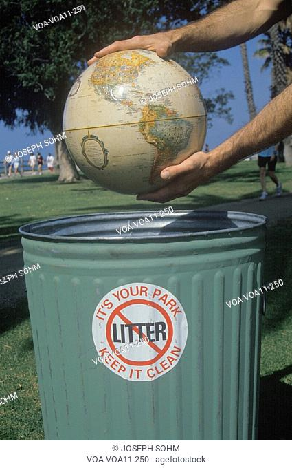 Hands holding a globe over a park trash receptacle