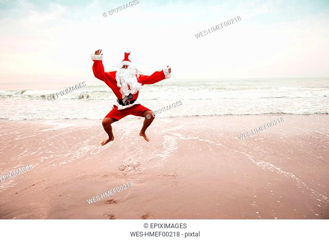 Thailand, man dressed up as Santa Claus jumping in the air on the beach