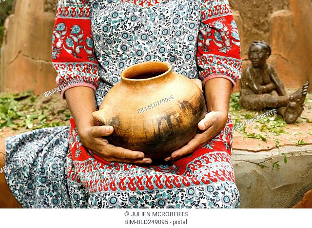 Woman sitting and holding clay pot