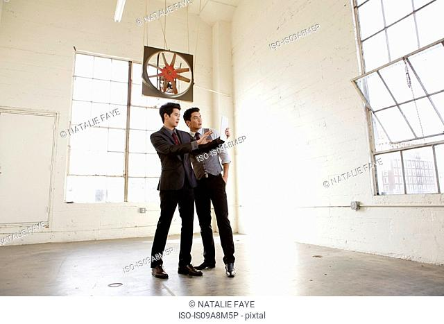 Two young men inspecting empty office