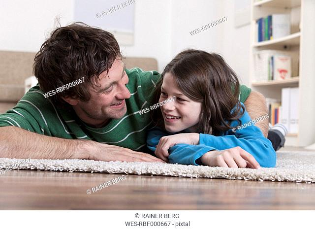 Germany, Bavaria, Munich, Father and son lying on carpet, smiling