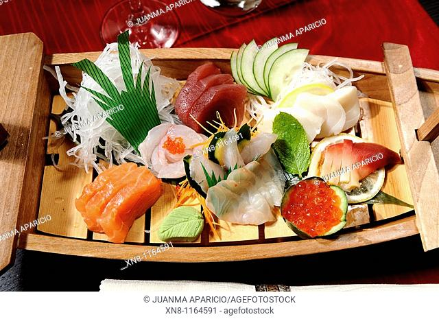 Combined Sashimi several types of fish in a nice presentation on wooden Ship