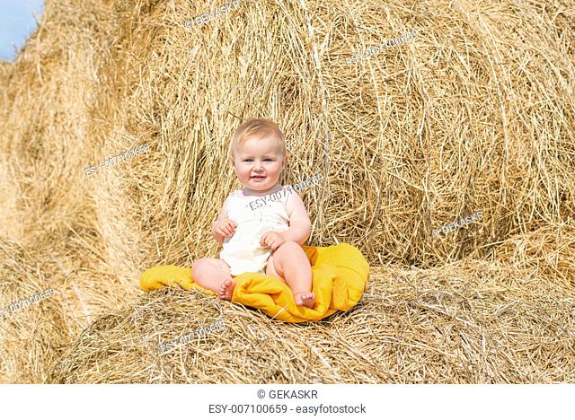 cute baby on stack of hay