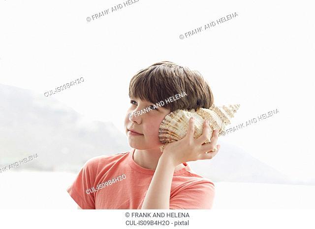 Boy holding seashell to ear, Kraalbaai, South Africa