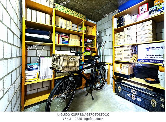 "Tilburg, Netherlands. Basement storage room of Studio Tuinstraat, with archive shelves and transport bike. Organising storage rooms is sometimes """"forgotten"""""
