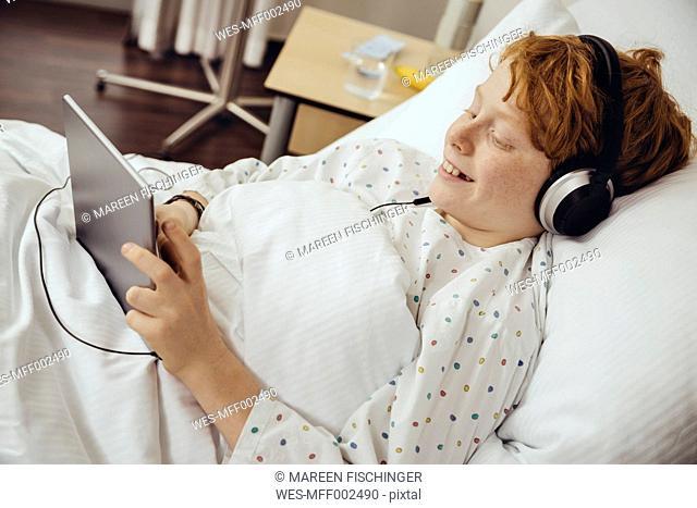 Sick boy lying in hospital using digital tablet, wearing head phones
