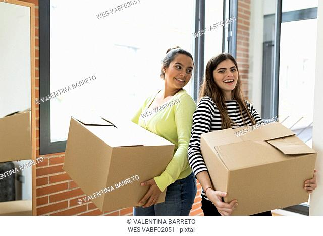 Portrait of two smiling young women carrying cardboard boxes in new apartment at the window