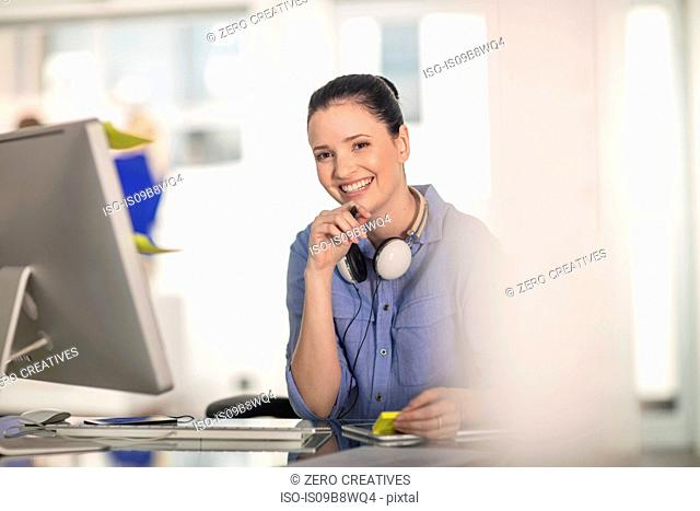 Portrait of young female office worker at desk
