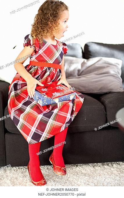 Girl sitting on sofa with Christmas gift
