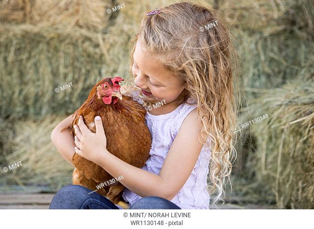 A young girl holding a chicken in a henhouse