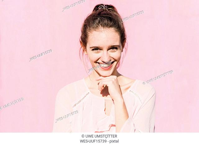 Portrait of smiling young woman in front of pink wall