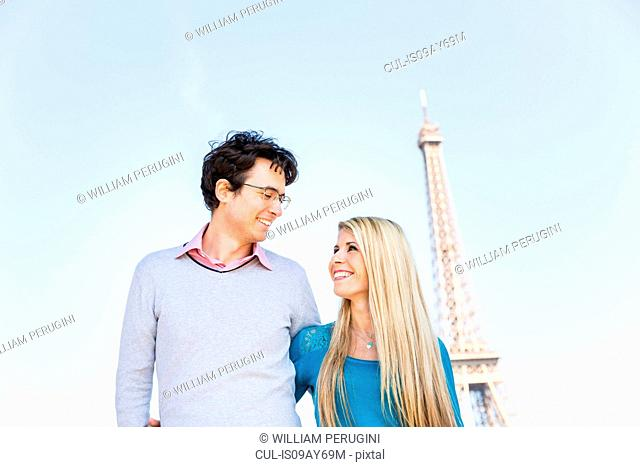 Couple in front of eiffel tower face to face smiling, Paris, France
