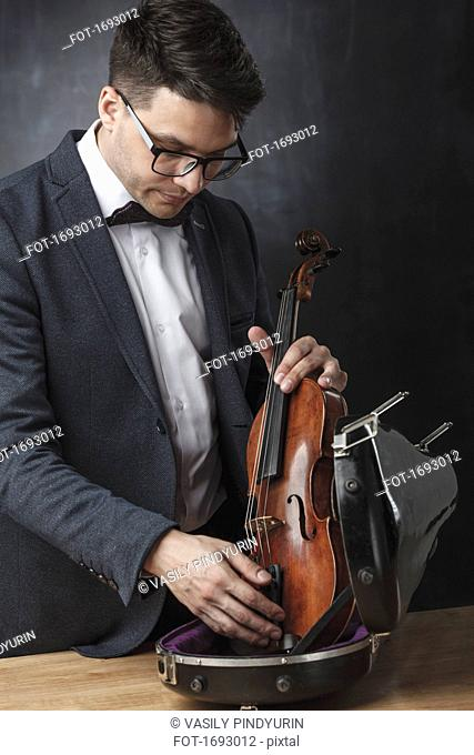 Young man keeping violin in case at table against black background