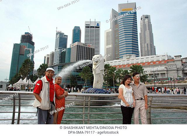 Old Indian couple standing near Merlion statue in Merlion park , Singapore MR
