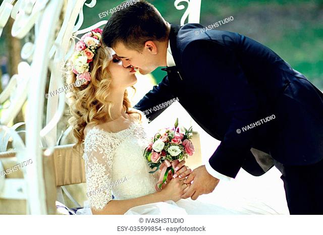 Handsome groom kissing blonde beautiful bride in magical fairy tale carriage close-up