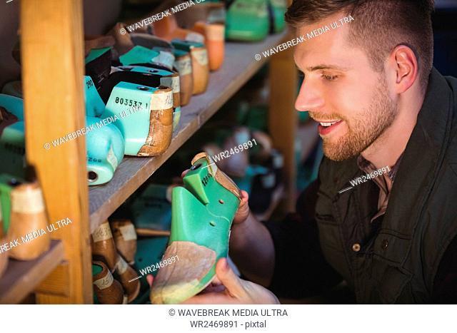 Cobbler holding a shoemaker in workshop