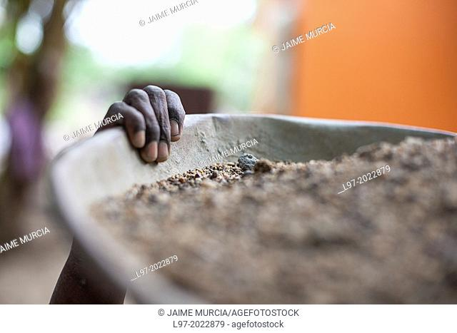 The hand of a woman holding a tub carrying gravel for construction, India