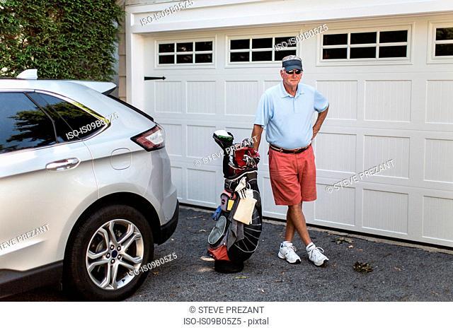 Portrait of senior male golfer standing next to garage door with golf bag