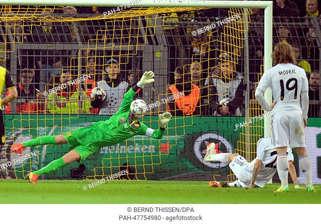 Dortmund's goalkeeper Roman Weidenfeller prevents Madrid's Di Maria from scoring a penalty shot during the UEFA Champions League quarter-final second leg soccer...