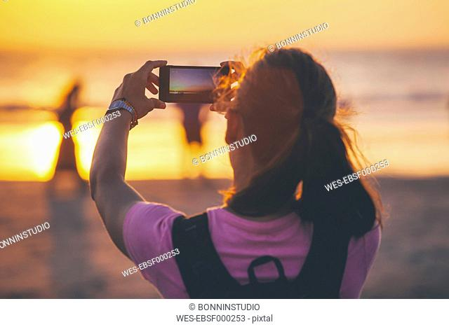 Indonesia, Bali, woman on the beach photographing sunset with her smartphone
