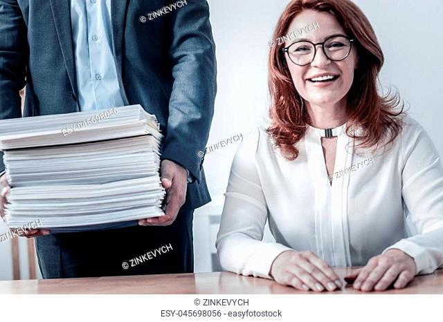 Positivity is the key to success. Selective focus on a male coworker holding a pile of different documents while standing next to his female colleague smiling...