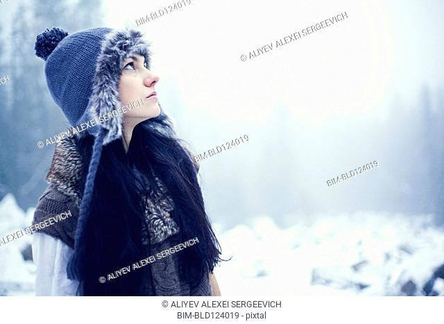 Caucasian woman standing in snowy woods