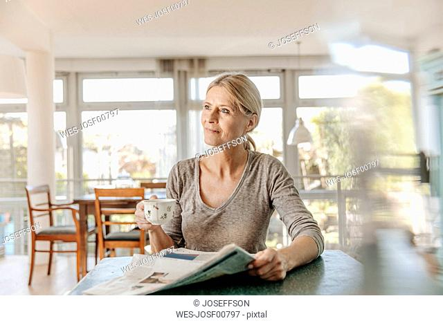 Woman at home sitting at table with cup of coffee and newspaper