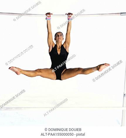 Young female swinging on uneven bars