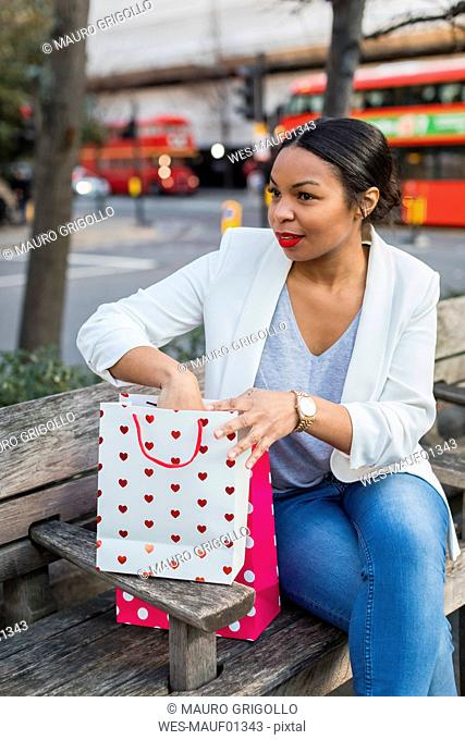 UK, London, woman with shopping bags sitting on a bench in the city