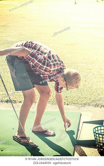 Young golfer setting up a tee off while practising at the driving range. Instagram style sports portrait