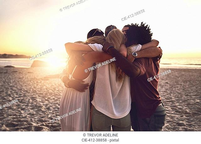Young friends hugging in a huddle on sunset summer beach