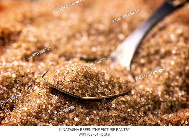 Brown sugar heap and close up of metal spoon