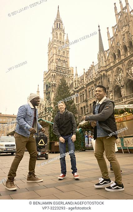 young men jumping in front of Neues Rathaus and Christmas market at Marienplatz in Munich, Germany